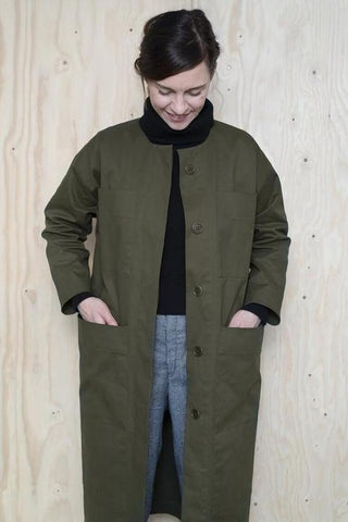 a white lady standing against a plywood background wearing a olive green long jacket with a black roll neck jumper and blue jeans underneath