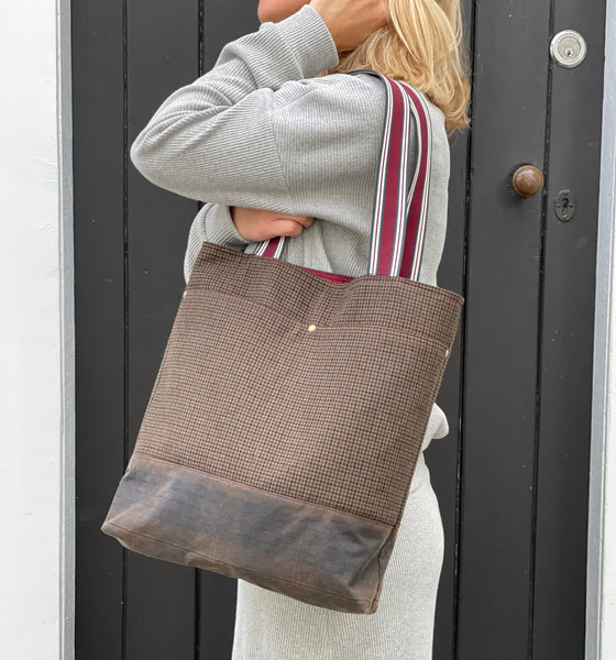 a wool and wax tote in a muted browns over the shoulder of a lady wearing grey. The tote bag is one third oilskin fabric at the base and the rest is wool with cotton webbing for the handles with a maroon stripe