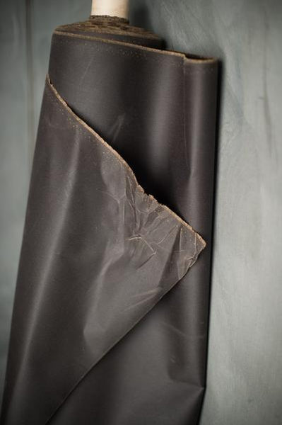 a photo of a roll of oilskin on a roll leaning up against a grey background. The fabric is slightly unravelling