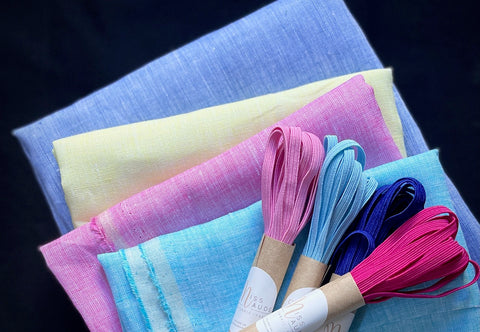a pile of fabrics with a blue on the bottom, yellow next, pink and then turquoise. with four coloured elastic on the top
