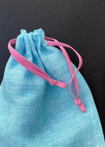 a photo of the finished bag in turquoise linen and pink elastic