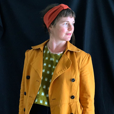 an image of a white woman wearing a dark yellow jacket and a green and white check top. she is looking to the bottom right of the screen and is wearing a rust coloured headband which she has made.