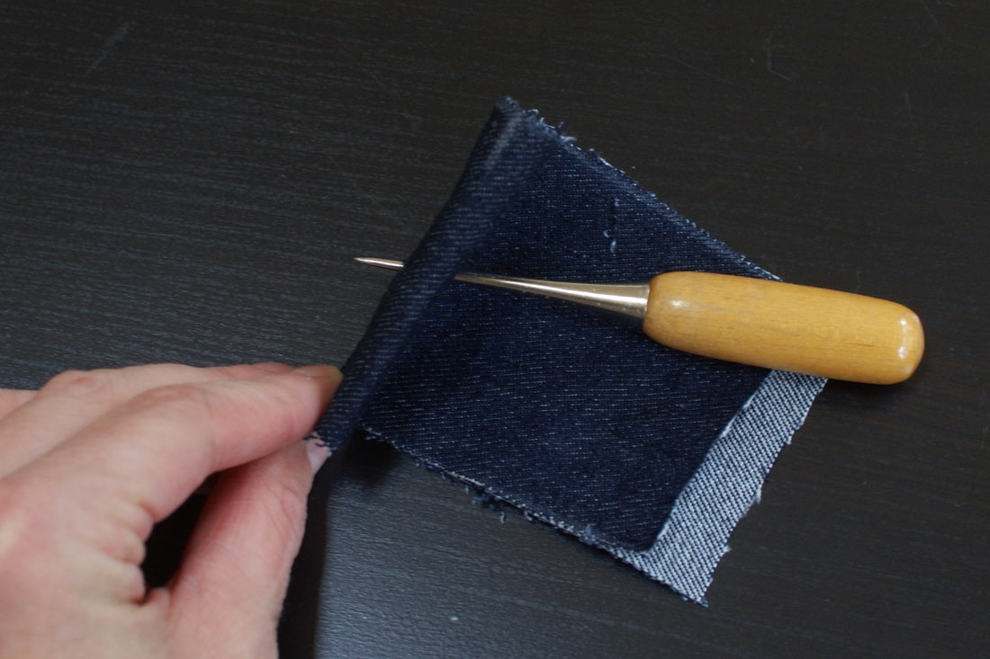 using an awl to install jeans buttons
