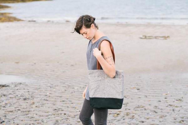 a white woman walking on a deserted beaching with a wool and wax tote bag prominently displayed, hanging over her shoulder.