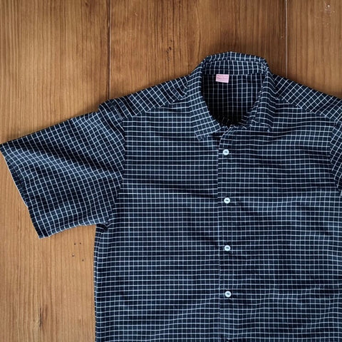mans black shirt sleeve shirt with white check, it has white buttons. The shirt is a flat lay on a polished wood floor.