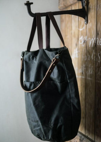 a black oilskin tote bag hanging on a black cast iron hook attached to a wooden wall