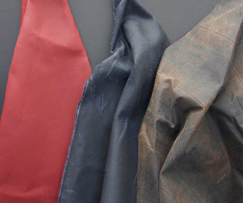 three oilskins draped over a black background from left to right the colours are deep red, black and brown