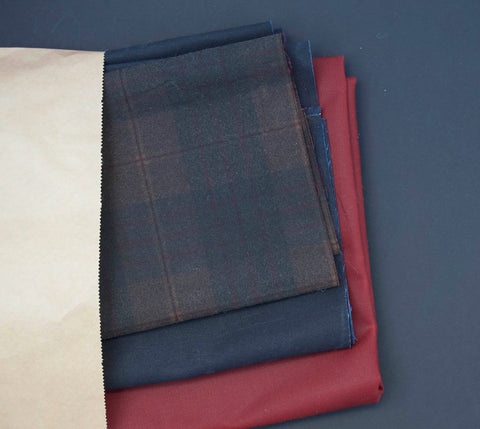 three types of oilskin coming out of a paper bag. The edge of the paper bag is on show on the left hand side and is a thin strip.
