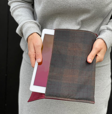a white woman pulling an iPad out of the case. She is wearing grey clothing