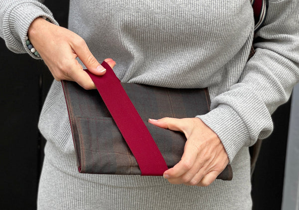 a white woman in a grey outfit is pulling the strap on the oilskin cover.