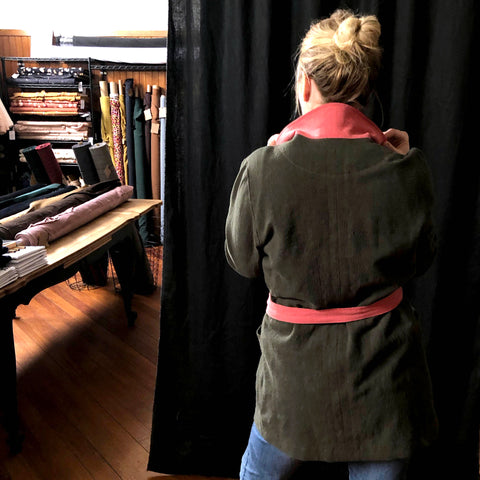 a picture of the coat on the lady. this time the photo is from the back. in the background of the photo there are bolts of coloured fabric on shelves and on a table.