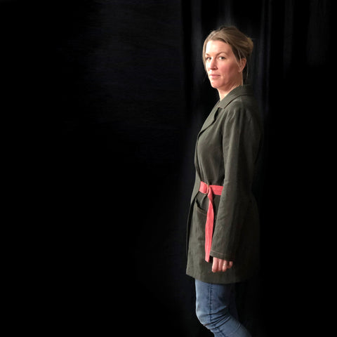 a picture of a lady looking moodily at the camera, it may have been taken at the end of the shoot when she was a bit over it. It is a side view of the lady and it is a dark background. She is wearing a khaki green coat made of linen with a pink belt. you can see a portion of her legs in jeans to show the coat is thigh length.