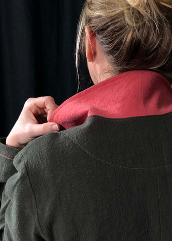 a close up of the lady from the earlier photos but taken from the back. It shows  the collar of the Sienna Maker Jacket up and the lady's hand is holding the collar. The back of the lady's head is showing and her hair is pulled up in a messy bun. The photo shows the pink topstitching on the green jacket.