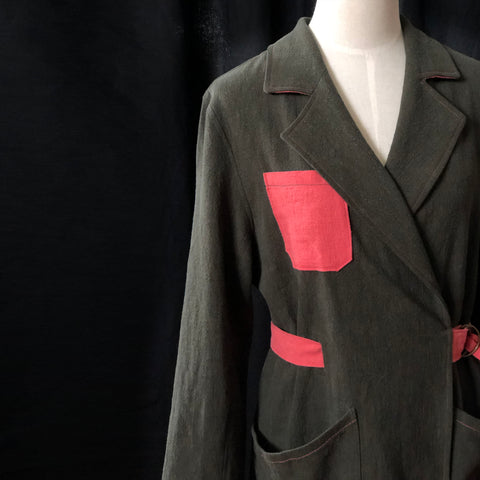 a picture of the Sienna maker jacket on a dressmakers bust. the green linen jacket has a salmon pink belt and pocket and shows off a lovely notched collar