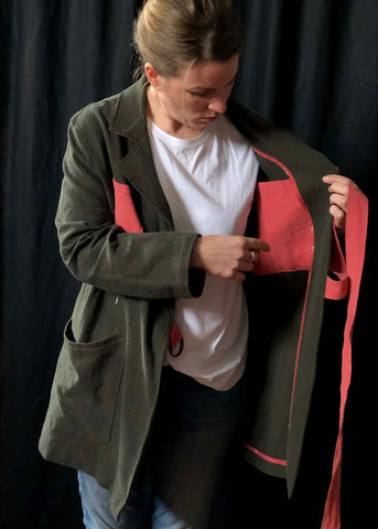 the wearer of the Sienna maker jacket has the jacket open and is pointing towards the interior pocket.