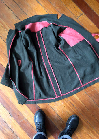 a photo of the inside of the jacket. It is laid on a wooden floor and is opened out. It shows how all of the seams have been bound by bias binding. It also shows the pink interior pocket with the jacket facing slightly over the top of the pocket.