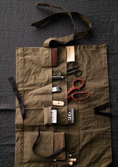 an image of a tool roll laid out on the table with a variety of sewing implements in the pockets.