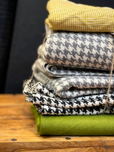 a pile of thick woollen fabrics folded on top of a wooden box