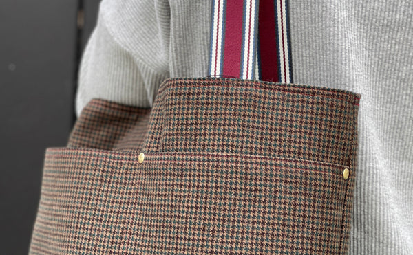 a close up of the where the handles of the bag meets the bag and shows the gold rivets installed at the pocket seams