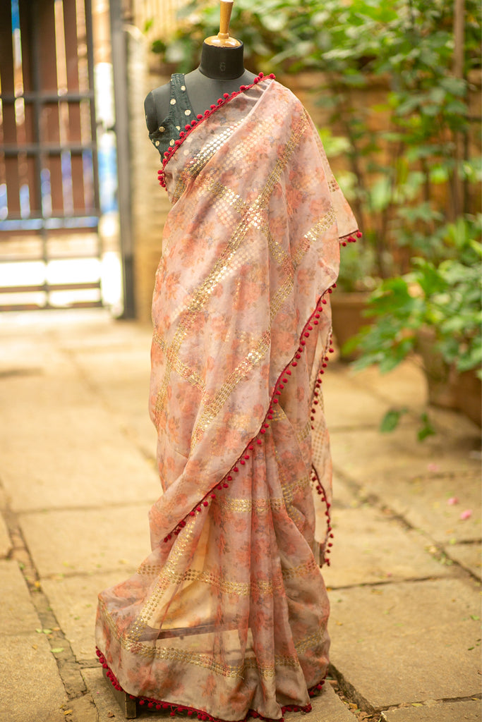 Peach floral printed organza saree with gold sequin work and red pompom edging - House of Blouse