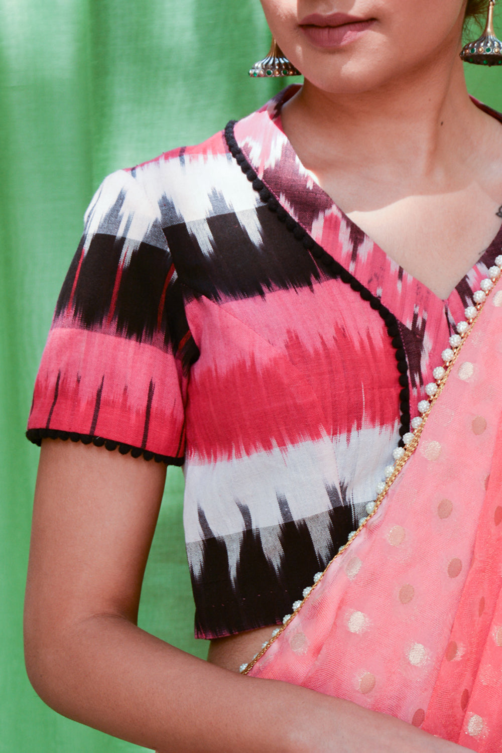 Pink, black and white Ikat cotton V neck blouse with black pom pom detailing