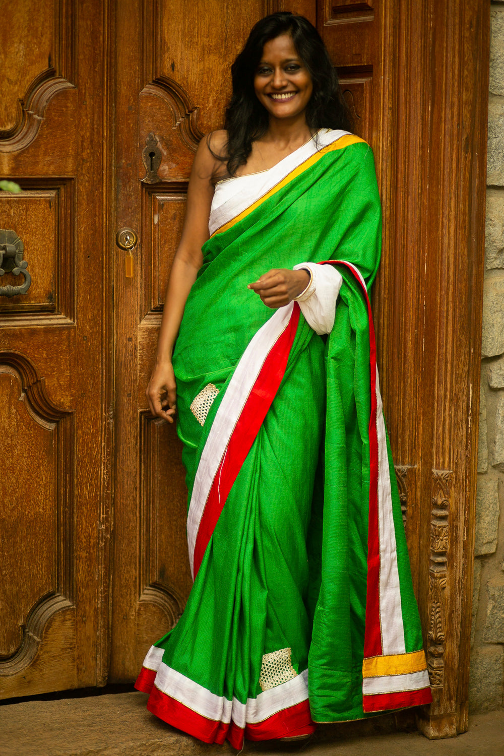 Forest green raw silk saree with red, white and yellow borders and disjointed lace detailing - House of Blouse