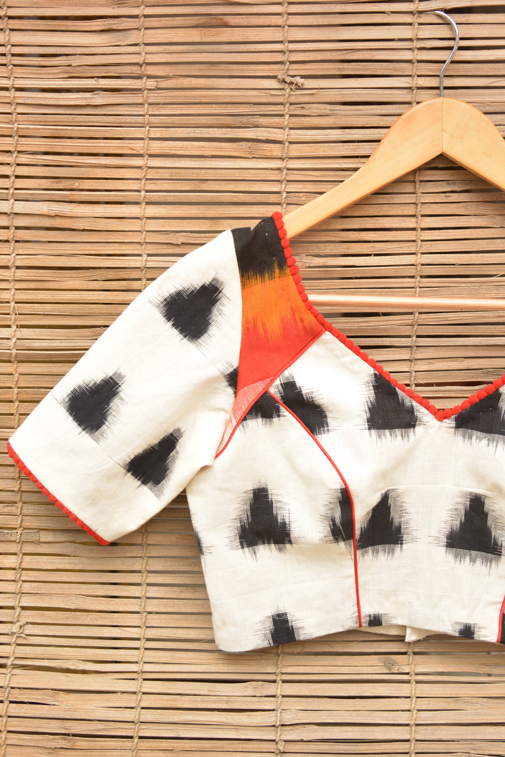 White and black Ikat cotton armband blouse with red pom pom detailing