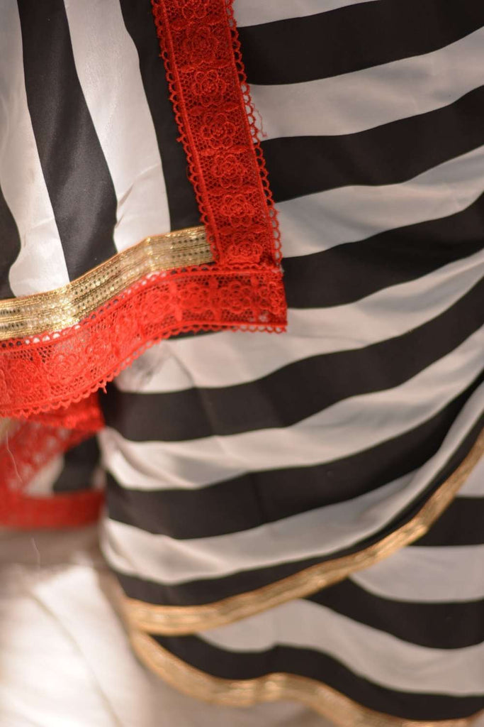 Black and white striped crepe saree with gold and red lace border