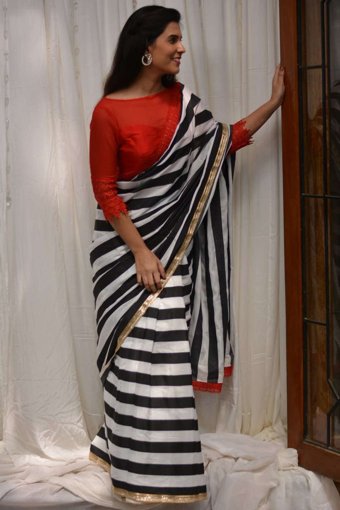 Black and white striped crepe saree with gold and red lace border - House of Blouse