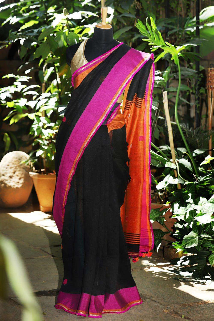 Black linen saree with pink and orange threadwork motifs and pink-gold frill edging