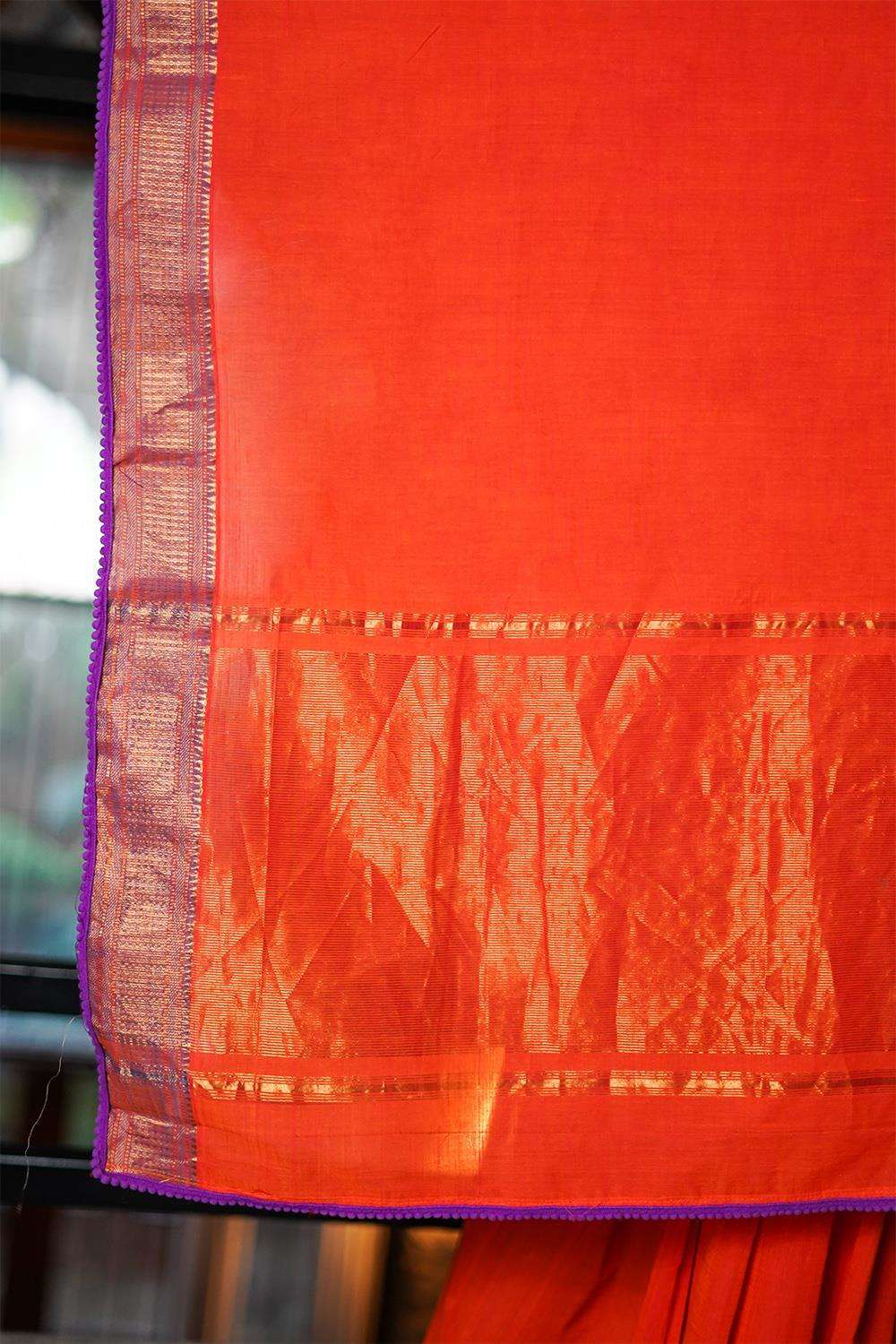 Orange Maheshwari handloom silk cotton saree with purple zari border and pom pom edging