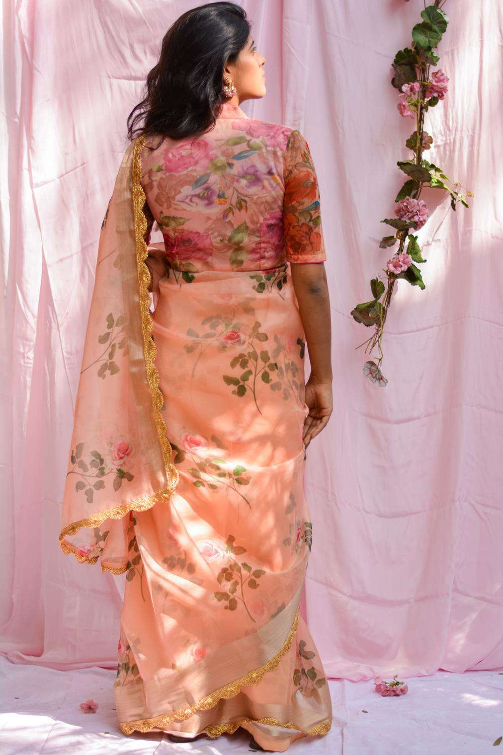 Peach floral printed organza saree with tissue border and scallop edging