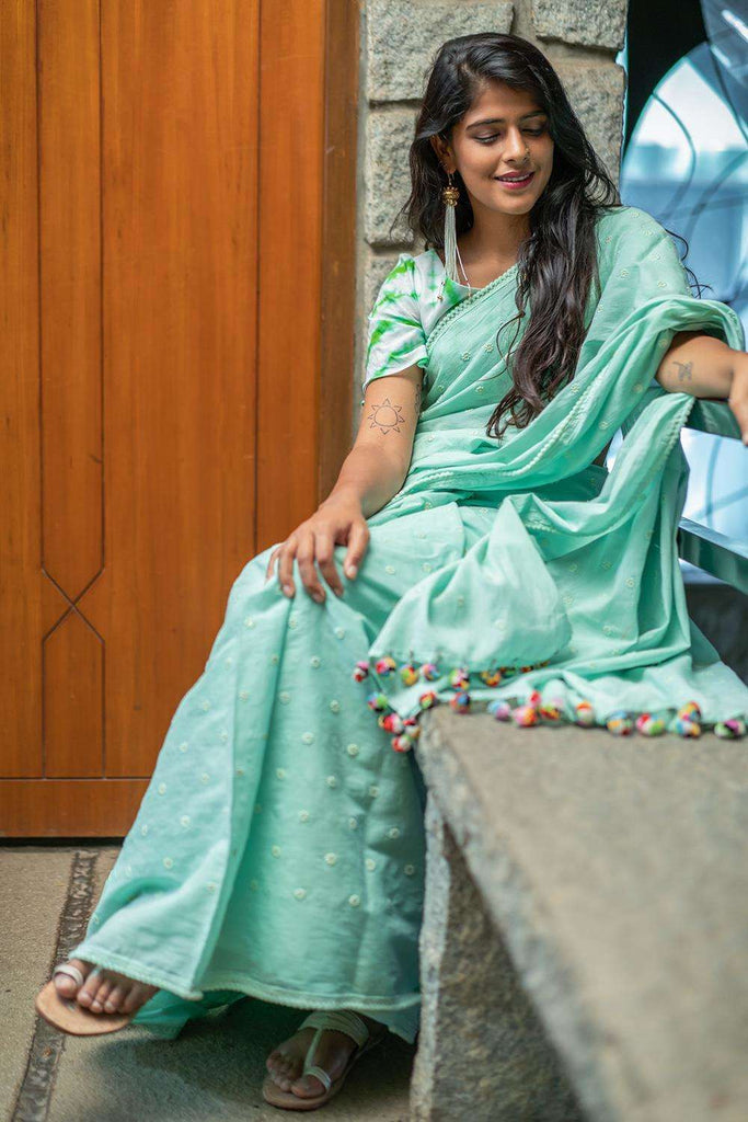 Sea green mul cotton saree with floral threadwork motifs and pom pom edging