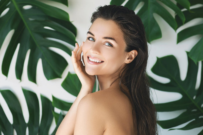 youthful young lady holding side of face tropical leaves 4 tips for summer skin health