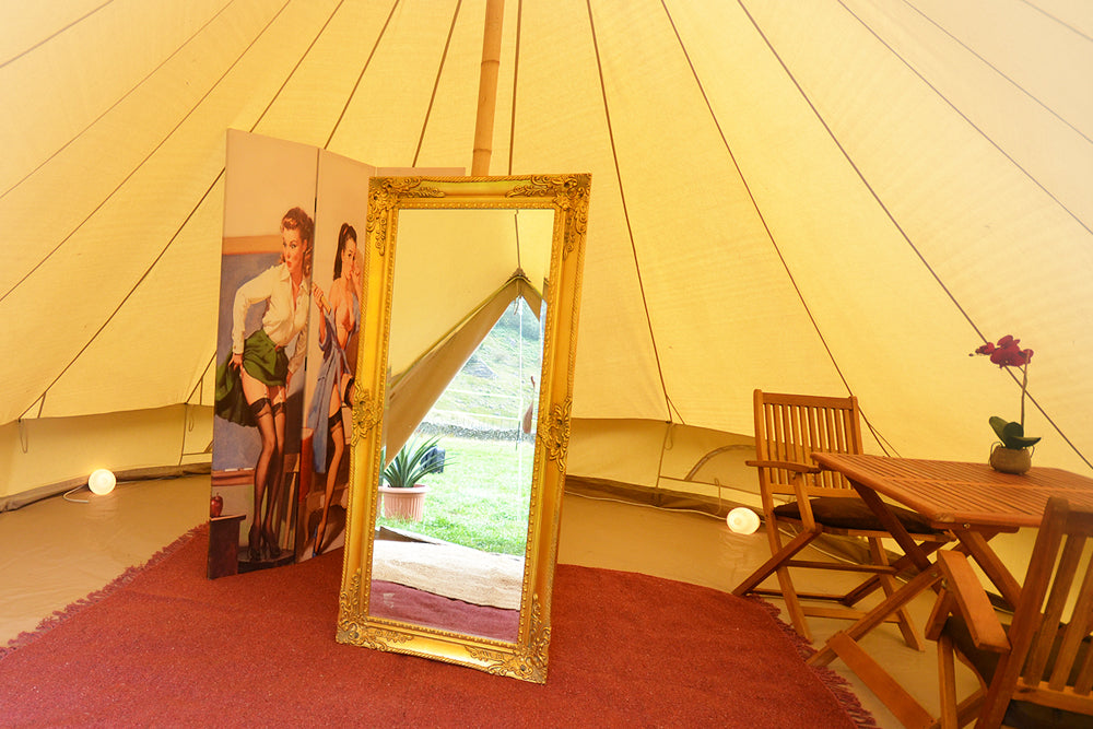 Bell tent interior with full length mirror table and chairs