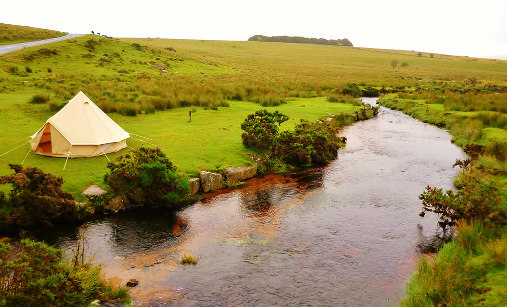 A beautiful bell tent pitched by the side of a stream.
