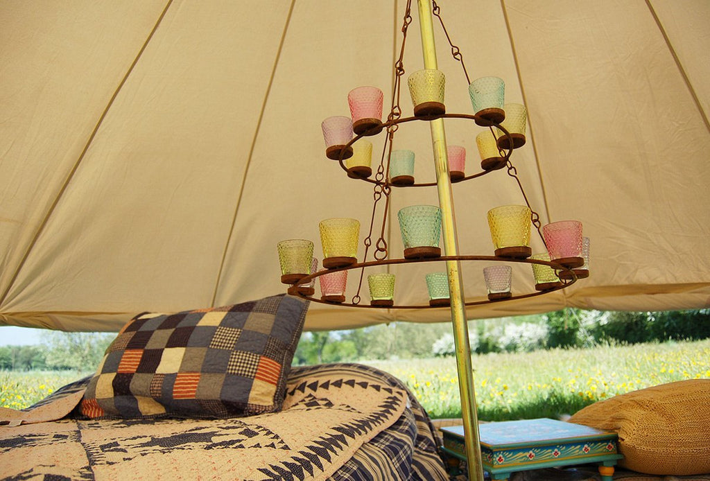 Double tier multi coloured glass tea light chandelier in a bell tent with the wall rolled up