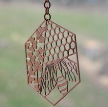 Load image into Gallery viewer, Copper suncatcher with a bee, clover & honeycomb design by Pittsburgh artist Audra Azoury.