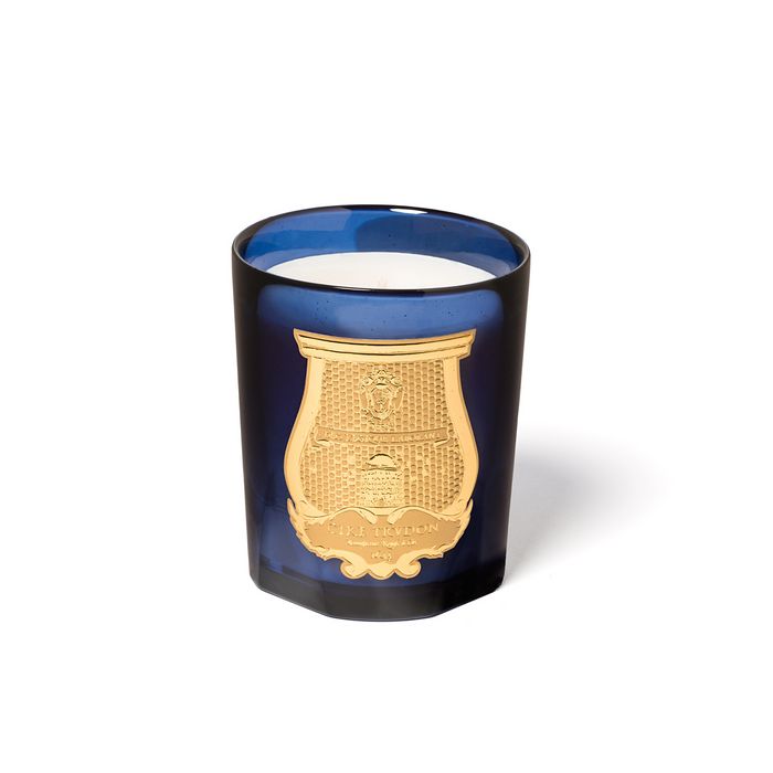 White candle in translucent blue glass jar with gold Cire Trudon emblem.