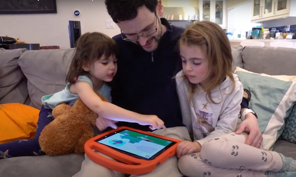 A father sits on a couch with his two young daughters, and they are looking at a Khan Academy Kids video together on an iPad.