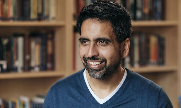 Khan Academy founder Sal Khan wears a blue sweater and smiles in front of a row of bookshelves.