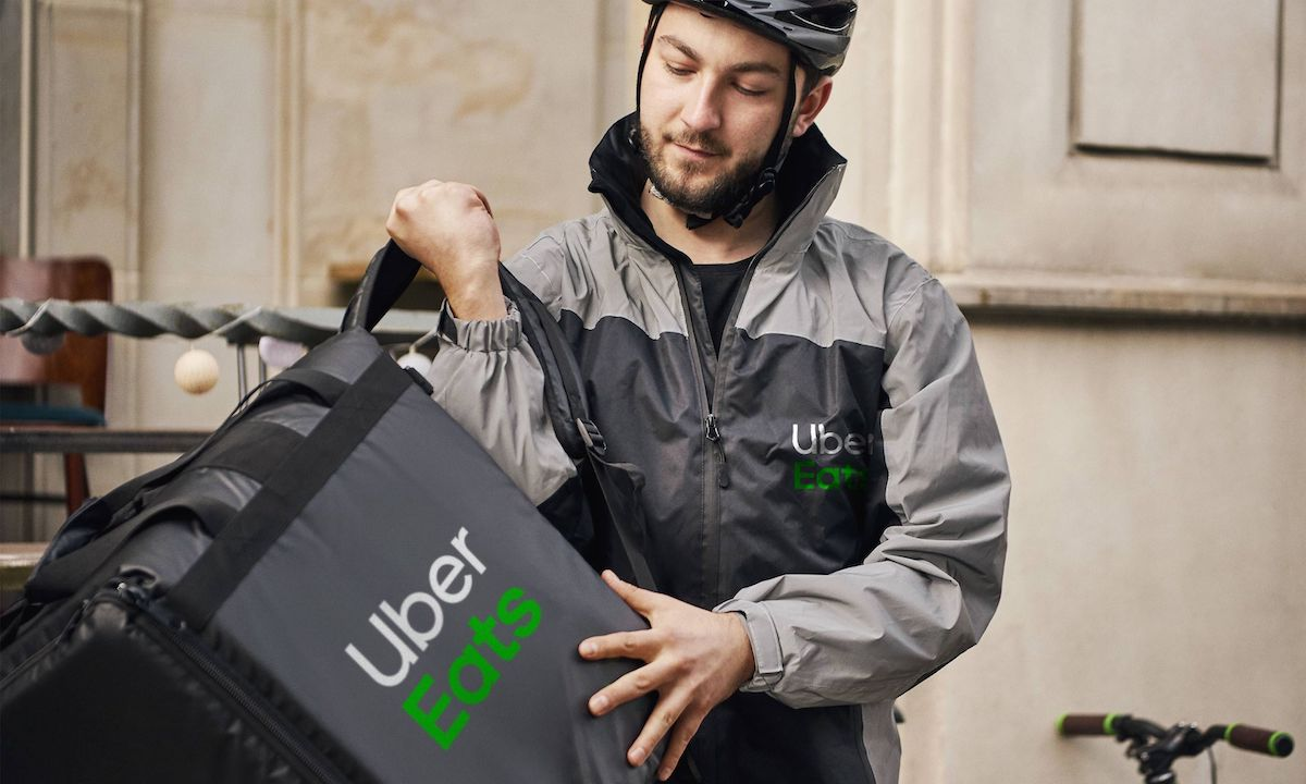 Person with a helmet and jacket holding a food delivery bag.