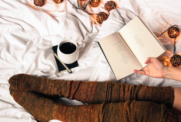 concept of hygge reading on bed with coffee