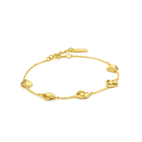 Image of a delicate gold chain link charm bracelet embellished with crushed gold disc charms by designer Ania Haie.