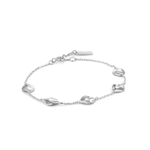 Image of a delicate silver chain link charm bracelet embellished with crushed gold disc charms by designer Ania Haie.