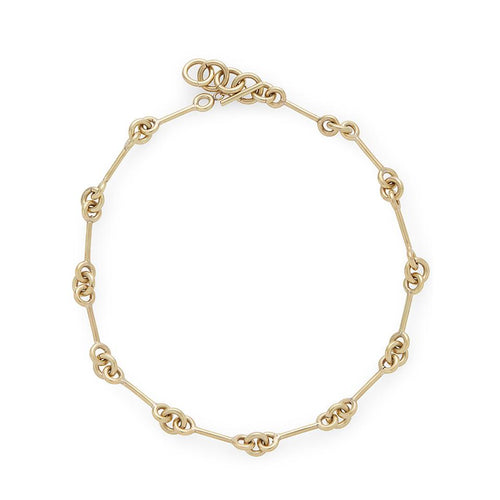 An image of a blonde model wearing a 24 karat gold necklace with a unique bar and loop format all the way around it, by Soko.