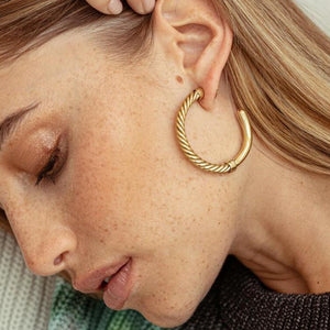 An image of a blonde model wearing a pair of 24 karat gold hoop earrings with a twisted wire detail by Soko