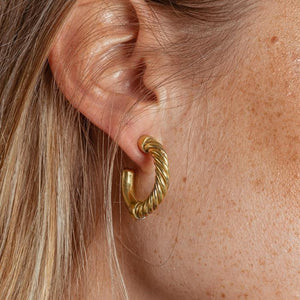 An image of a blonde model wearing a pair of 24 karat gold mini hoop earrings with a twisted wire detail by Soko