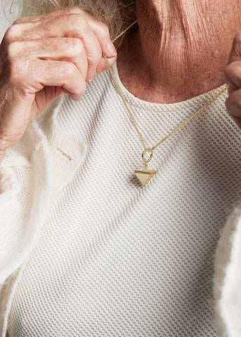 Upper body of old female wearing beige clothes and holding gold necklace named 115 40