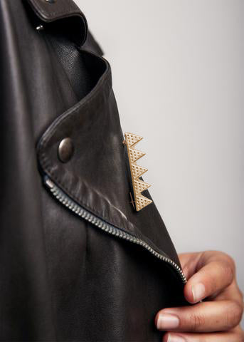 Close up of side of leather jacket with gold brooch named 126 53